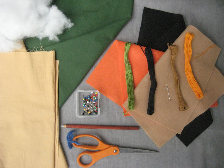 Materials! Here's what you'll need to make it happen:<br /><ul> <li>• 1/3 yard green fabric. I used a light cotton twill, but Bonnie used fleece in the book. Anything goes!</li><br /> <li>• 1/4 yard tan fabric</li><br /> <li>• Orange, black
