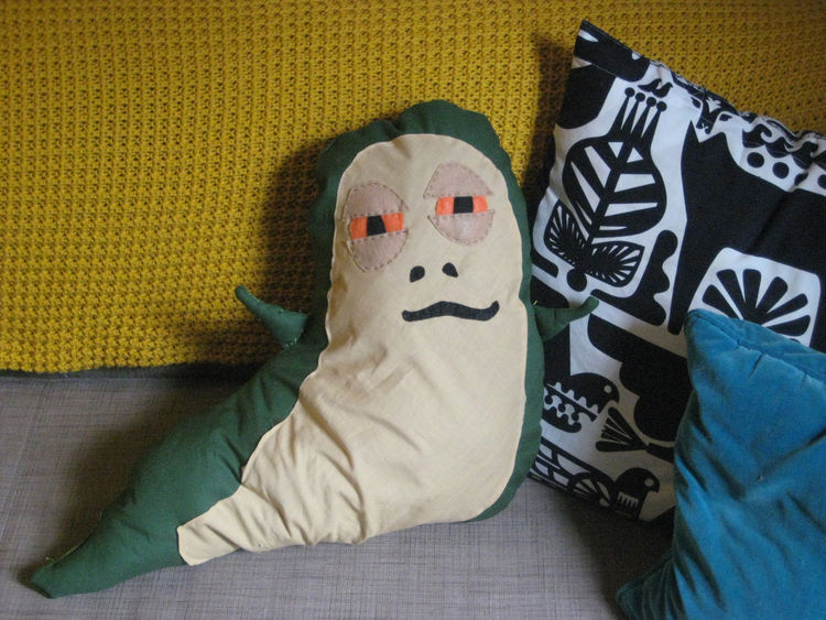 And here's Jabba, just chilling with his new pillow pals in his new home, my sofa. I have to admit, just looking at him makes me laugh, and he's actually a comfy addition to the living room scene.
