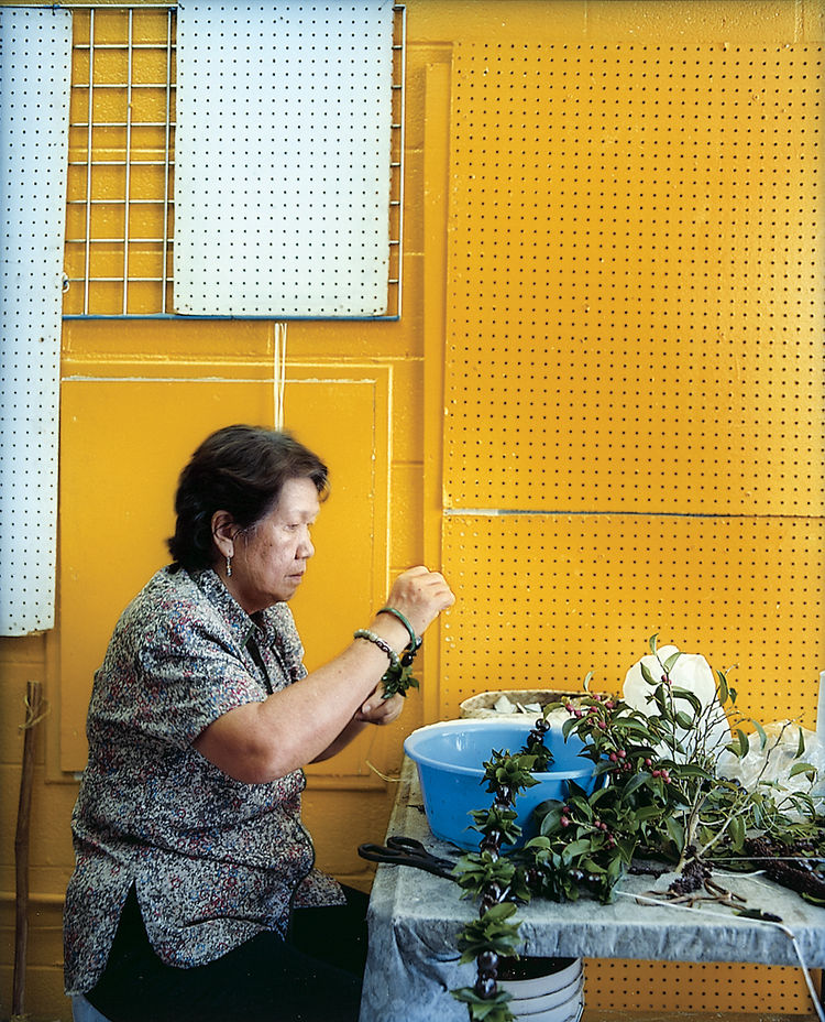 A woman strings kukui nuts and mock orange leaves at Jenny's Lei Shop in Chinatown.