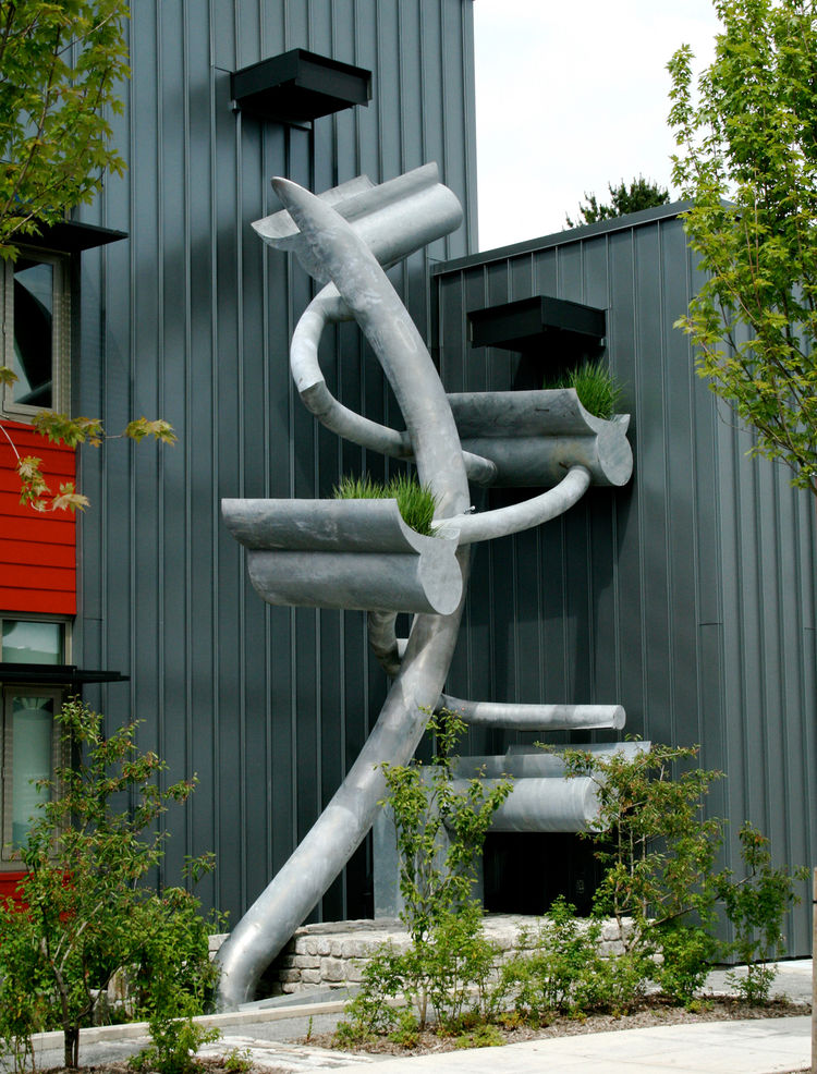 "<strong>""Thornton Creek"" by Stephen Glassman</strong><br /><br /> This steel sculpture literally serves to revive Thornton Creek, lost to urbanization. The reclaimed pipes were peeled open and now convey water from the rooftop of Fire Station 39 to an und"