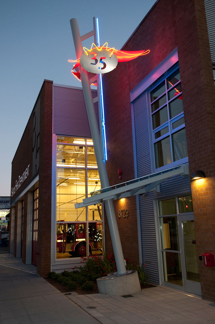 "<strong>""Rescue"" by Kay Kirkpatrick</strong><br /><br /> The abstracted ladder pushes away from the new Fire Station 35 as a reference to the rescues firefighters perform daily. Surrounding the playful ""35"" sits a neon crown of fire, both an obvious tie t"