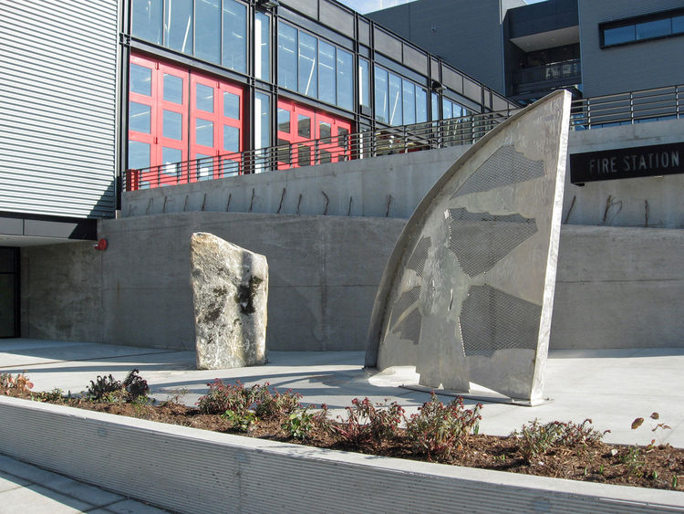 "<strong>""Call and Response"" by Stuart Nakamura</strong><br /><br /> Known in the Seattle Fire Department as ""the rock,"" the large boulder's etched lines and the accompanying stainless steel arc invite water imagery for those entering Fire Station 10. Insi"