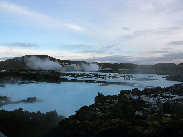 "The <a href=""<a href=""http://en.wikipedia.org/wiki/Svartsengi_Power_Station""> Svartsengi </a> geothermic power plant (in the background) looms over lava fields and feeds the large Blue Lagoon swimming area. The plant's runoff, heated by lava to hot-tub-pe"
