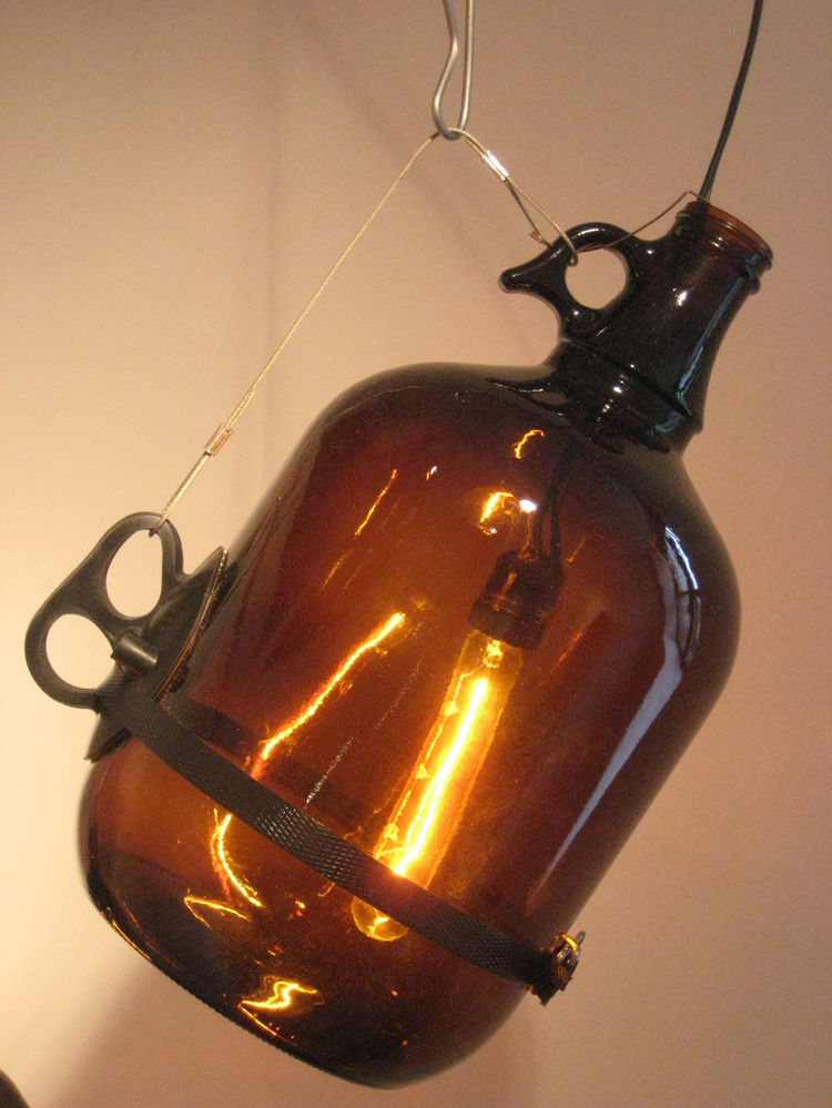 A close-up of a McMasterpiece pendant lamp by David Weeks, made with a tubular incandescent bulb and a glass jug.