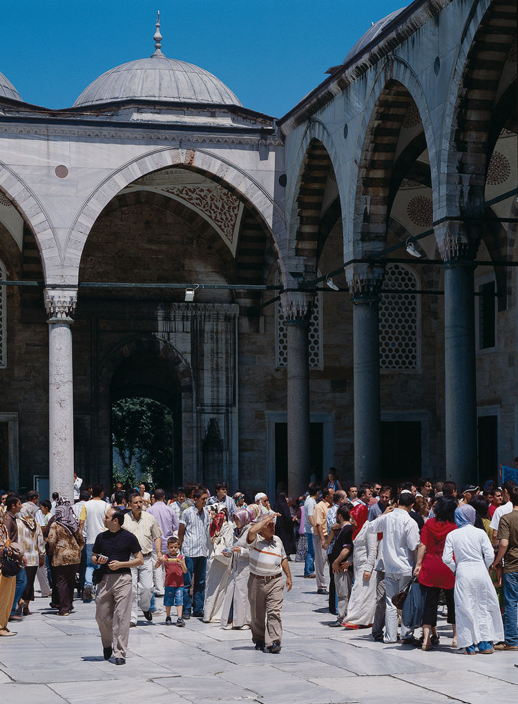 Devout Muslims and Western-style tourists congregate outside the Blue Mosque in the Sultanahmet district.