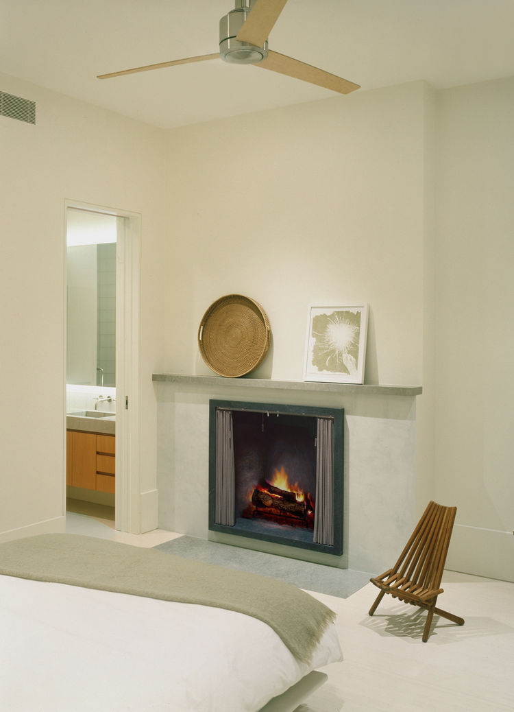 The firebox in the master bedroom is soapstone, which stores and slowly releases the heat of the fire. The limestone hearth is recessed flush with the whitewashed bamboo floor.
