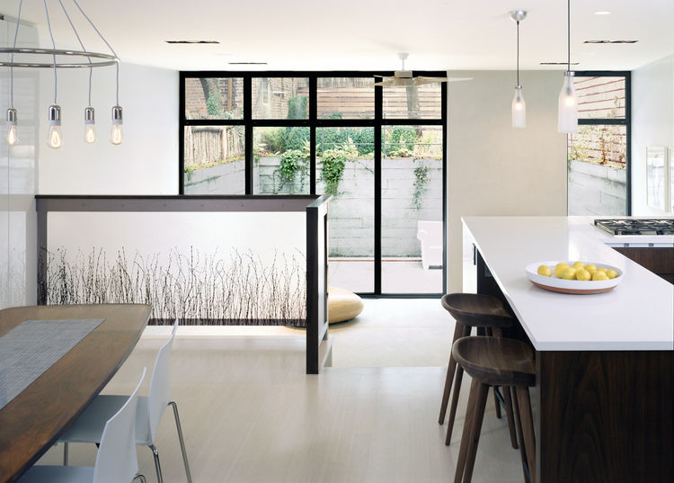 The apartment expands as you pass through it: the hallway broadens into the kitchen and dining room, which drops into the taller living room, which in turn opens onto the outdoor courtyard.