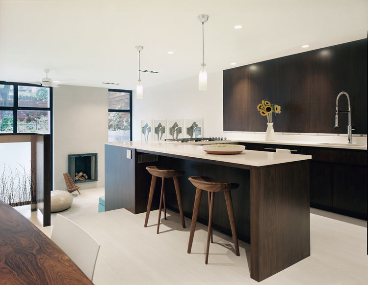 """To keep the open space from screaming 'kitchen,' we avoided upper cabinets,"" says Sherman. Instead, the storage is hidden behind full-height white lacquered panels. At the sink wall, the thin stainless steel line that separates the flush anigre panels fr"