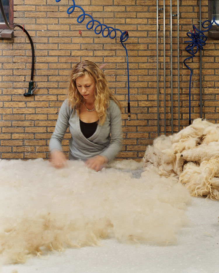 A felt maker lays Drenthe wool and raw silk onto a large table lined with bubble wrap.