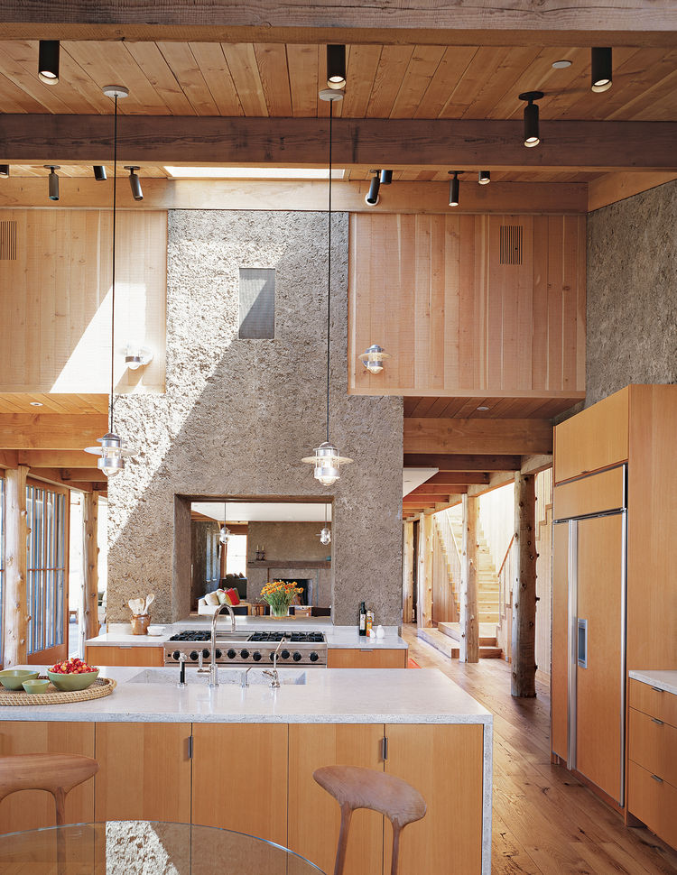 "The house has the feel of a refined barn: The kitchen flows into the dining area, then into a den. The two PISE ""chimneys"" serve to demarcate the transitions and visually unite the space."