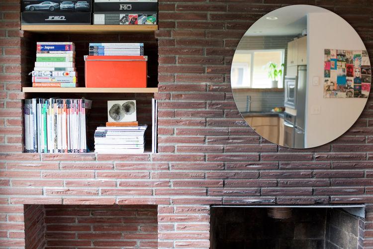 Michelle kept the character of the mid-century home intact, but didn't mimic the style in her new alterations. For example, she kept the Roman brick fireplace, which became a storage space.