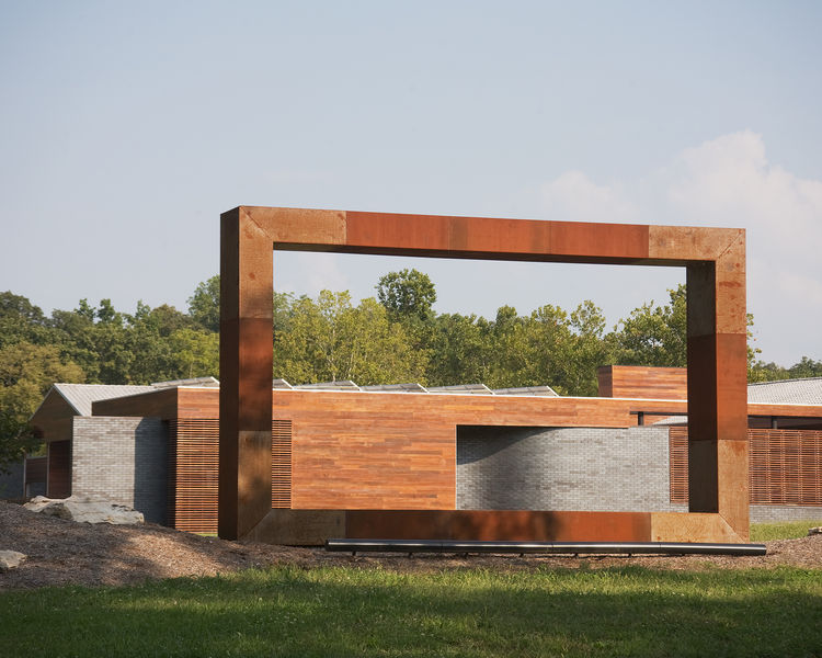 The Aperture, installed at the Curved House, was fabricated by MAKE Studios and frames the view of the nearby landscape in hot and cold rolled steel.