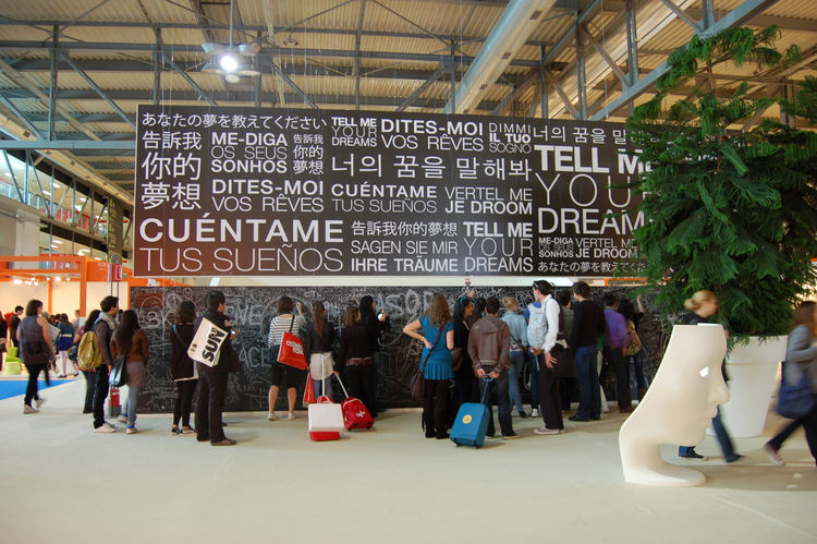 A huge chalkboard marks the entrance to Salone Satellite. Pieces of chalk suspended by string hang from the ceiling, and passersby are encouraged to record their scribbles.