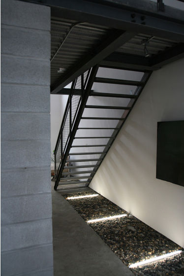 "A concrete pathway leads to the steel stairway to the sleeping loft, beneath which is a decorative ""garden"" of rocks with fluorescent tube lighting. Photo courtesy <a href=""http://www.linebox.ca/"">Linebox Studio</a>."