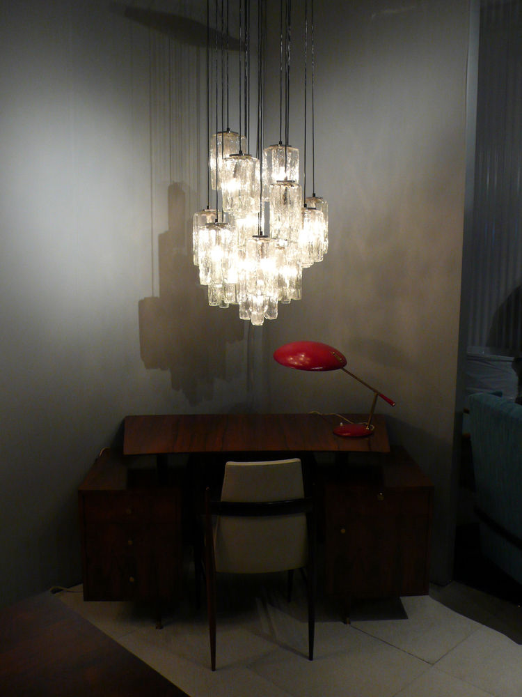 "<a href=""http://adessoimports.com/2006/index.php"">Adesso</a> filled a corner with a 1950s jacaranda desk by Joaquim Tenreiro, a 1950s Louis Kalff table lamp and a Kalmar chandelier."