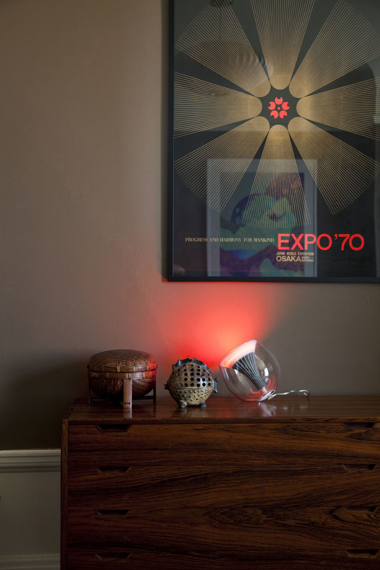 "A <a href=""http://www.coloryourworldsweeps.com"">LivingColors</a> lamp, resting next to a blowfish-shaped Japanese lantern, emits a concentrated beam of red light beneath a silk-screen print promoting Osaka's Expo '70."