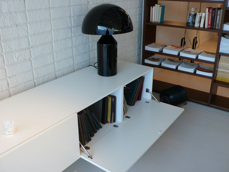 A low storage unit holds boxed LPs and an Atollo lamp by Oluce.
