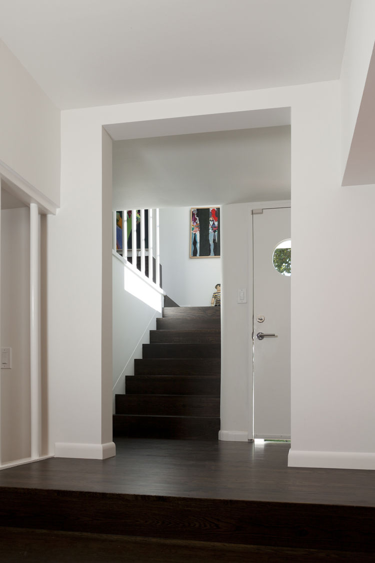 """The entrance, its front door accented by a porthole window, leads to stairways down to the media room and up to the living room and bedrooms. Photo by <a href=""""http://mikegraffigna.com/"""">Mike Graffigna</a>"""