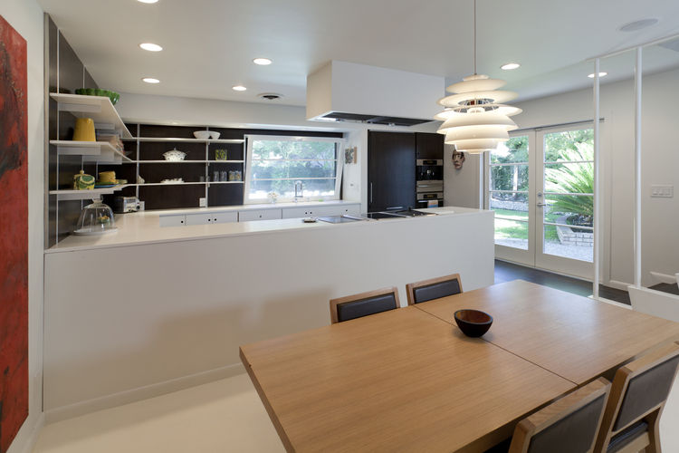 Popp closed off the cooking island to create a bar and countertop and stained the kitchen's white-oak walls brown to set off the space from the otherwise overwhelmingly white area. To bring more light and flow to the space, Popp replaced a small window wi