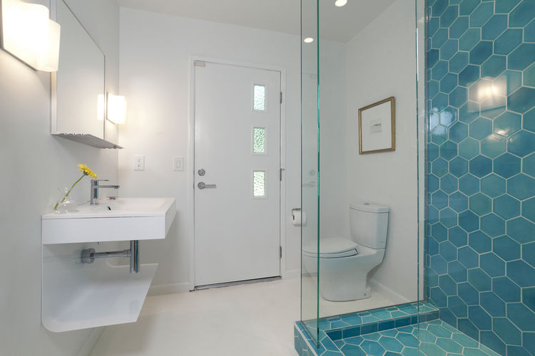 "The architect designed the vanity for the first-floor bathroom, which opens to both the media room and the backyard. Though he went with ""seconds"" tile elsewhere, for this bathroom Popp sprung for the hexagonal blue tiles from the latest collection by <a"