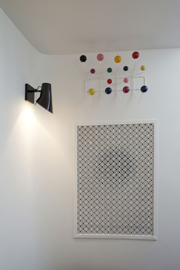 "An Eames Hang-It-All is above a new HVAC grate that replicates the originals in the house. Photo by <a href=""http://mikegraffigna.com/"">Mike Graffigna</a>"