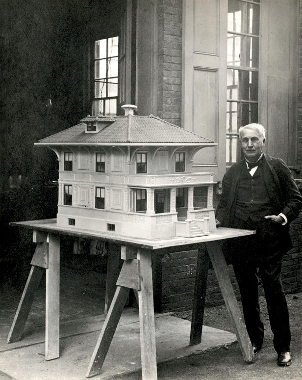 """Inventor Thomas Edison stands next to a model of a """"single-pour"""" concrete home, a progenitor of today's prefab."""