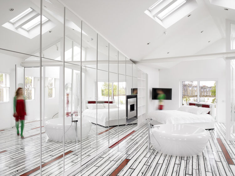 """We edited down until the house just became a pure white box,"" Rogers says. ""By the end of it all, we rethought everything except the internal walls."" The bright, skylit master bedroom is accented with <a href="" http://www.richardwoodsstudio.com/"">Richard"