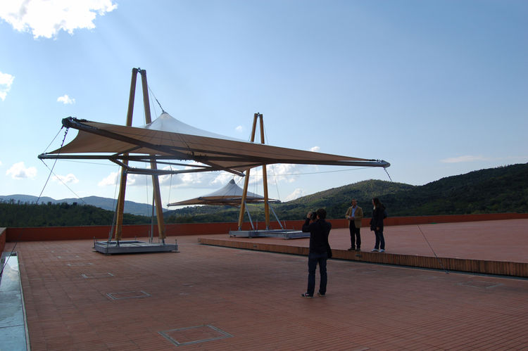 Massive sun shades designed by Piano are set up on the piazza; when it's time to process the grapes, they protect the fruit from the intense sunlight. At left, on the ground, is a narrow channel that opens to receive the grapes, which travel down a chute