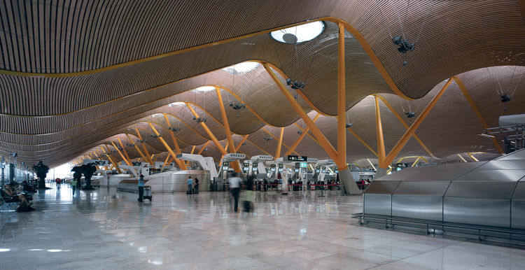 Madrid's intensely spacious Barajas Airport, completed in 2005, includes a massive sequence of color-coded columns, each vaulting up to the bamboo ceiling from massive plinths.