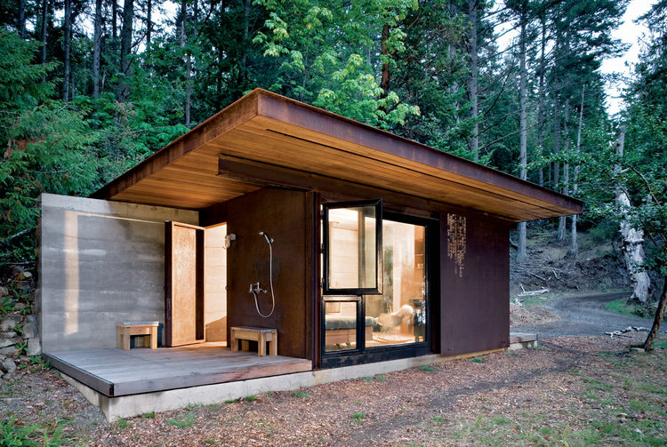 "This 191-square-foot cabin near Vancouver and its glass facades ""forces you to engage with the bigger landscape,"" architect Tom Kundig says, but it seals up tight when its owner is away. The unfinished steel cladding slides over the windows, turning it in"