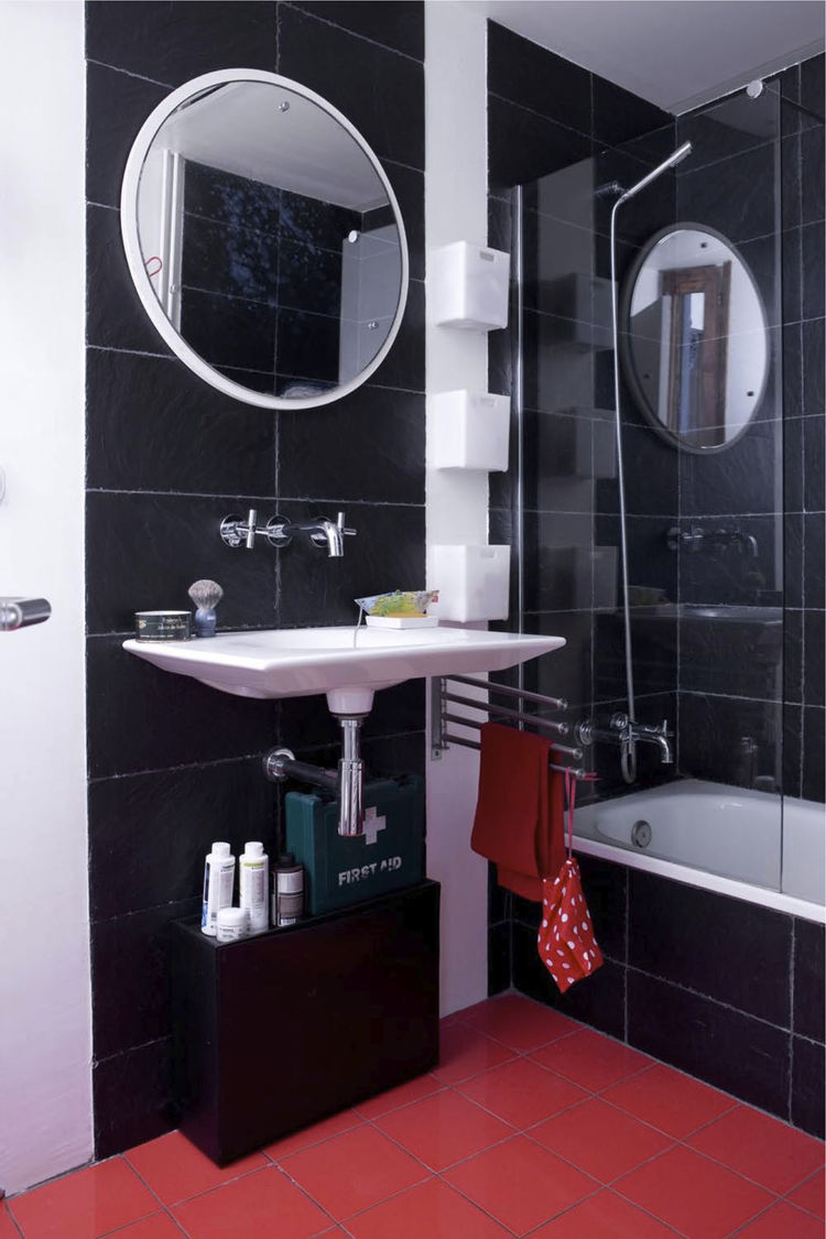 """In the bathroom, recycled plastic tiles surround the tub. Designed by Ramón Benedito for Roca, the Kalahari sink was fashioned from a single piece of ceramic. """"There's less waste than the standard sink,"""" says Scholtus, who also installed low-flow aerators"""
