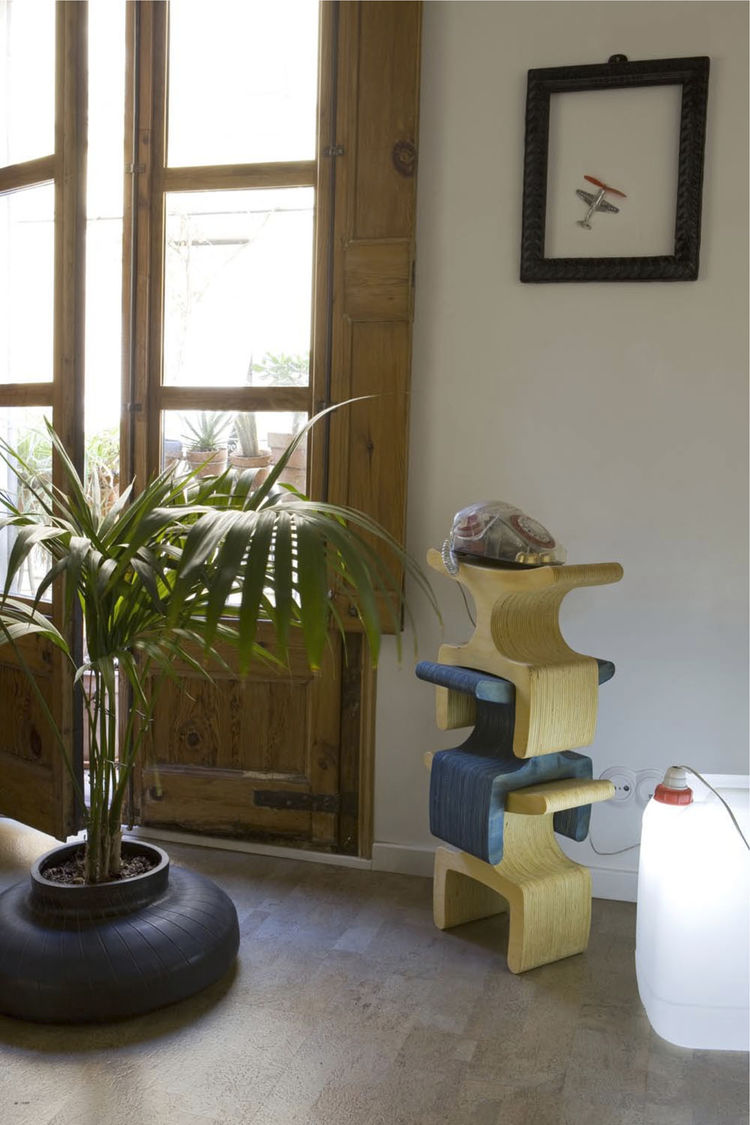 """An old tire finds new life as a planter, while the Enzo Stool by Ryan Frank serves as a telephone stand. The lamp at right was crafted using a discarded plastic container. """"We like objects made from few and easily identifiable materials, to ensure that th"""