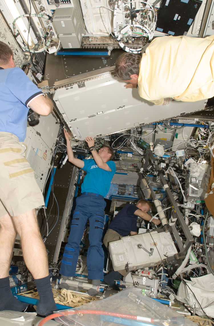 European Space Agency astronauts Christer Fuglesang (top foreground), STS-128 mission specialist; and Frank De Winne, Expedition 20 flight engineer, install a Materials Science Research Rack-1 (MSRR-1) in the Destiny laboratory of the ISS. NASA astronaut