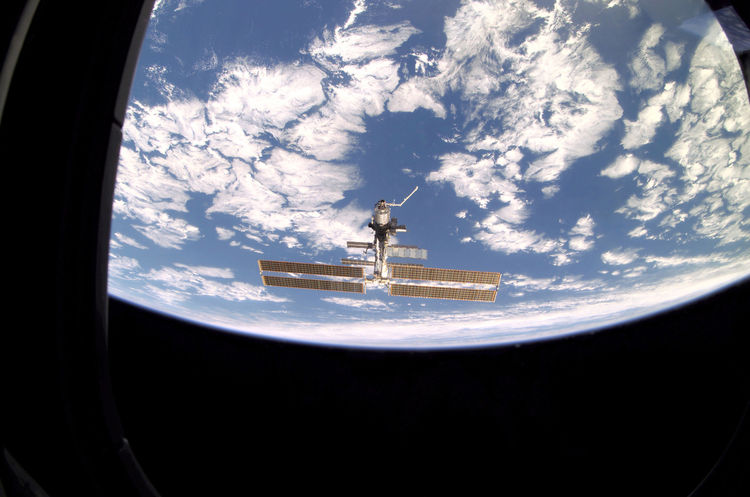 As seen through a window on Endeavour's aft flight deck, the ISS, then staffed with its fourth three-person crew, is contrasted against Earth's horizon during a farewell look from the shuttle following undocking. Photo taken December 15, 2001. <br /><br /