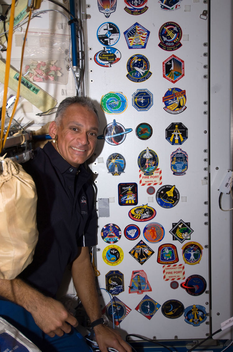 "NASA astronaut John ""Danny"" Olivas, STS-128 mission specialist, poses for a photo with the growing collection, in the Unity node, of insignias representing crews who have worked on the ISS.Photo taken September 7, 2009. <br /><br />Courtesy of NASA"