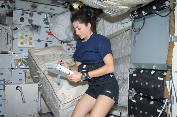 Astronaut Nicole Stott, STS-128 mission specialist, looks over a checklist on the middeck of Space Shuttle Discovery during flight day two activities. Photo taken August 29, 2009. <br /><br />Courtesy of NASA
