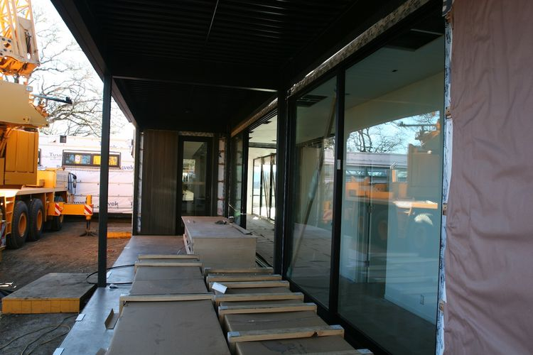 A view down the length of the outdoor covered deck leading to the front door.
