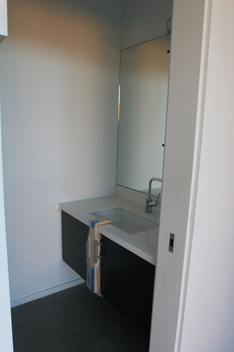 A view into the guest bathroom. The sink, fixtures, cabinets and mirror were already in place when the module arrived on site; they were installed in the factory.