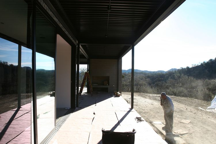 A view of the outdoor covered deck off of the living room, looking towards the concrete block fireplace.