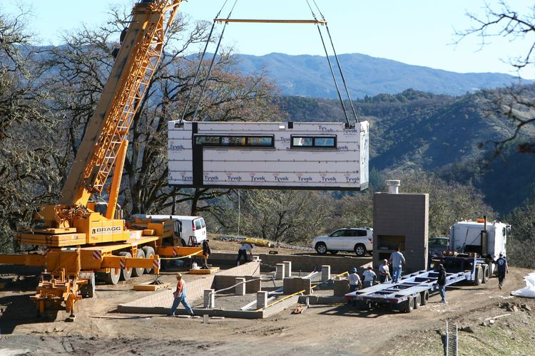 The first module (part of the master bedroom) is lowered into place.