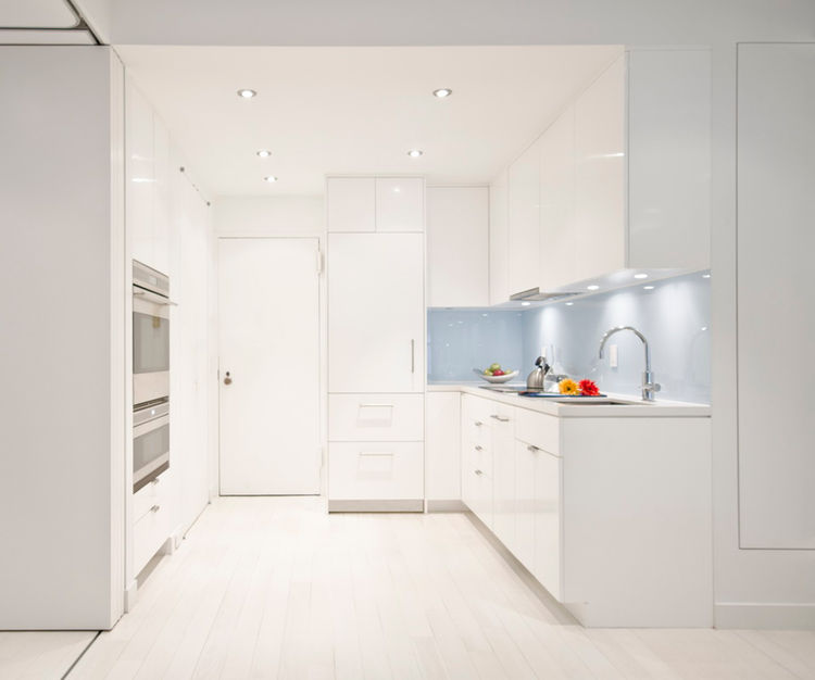 The kitchen features Caesarstone countertops, a Miele dishwasher and hood, SubZero refrigerator, and built-in microwave and oven by Wolf.