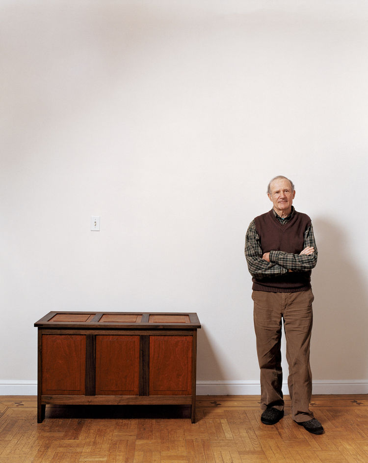 Simon Watts stands next to a mahogany-and-walnut chest—just one of many pieces he has rebuilt to replace all of the furniture that was mysteriously taken from his home last year.