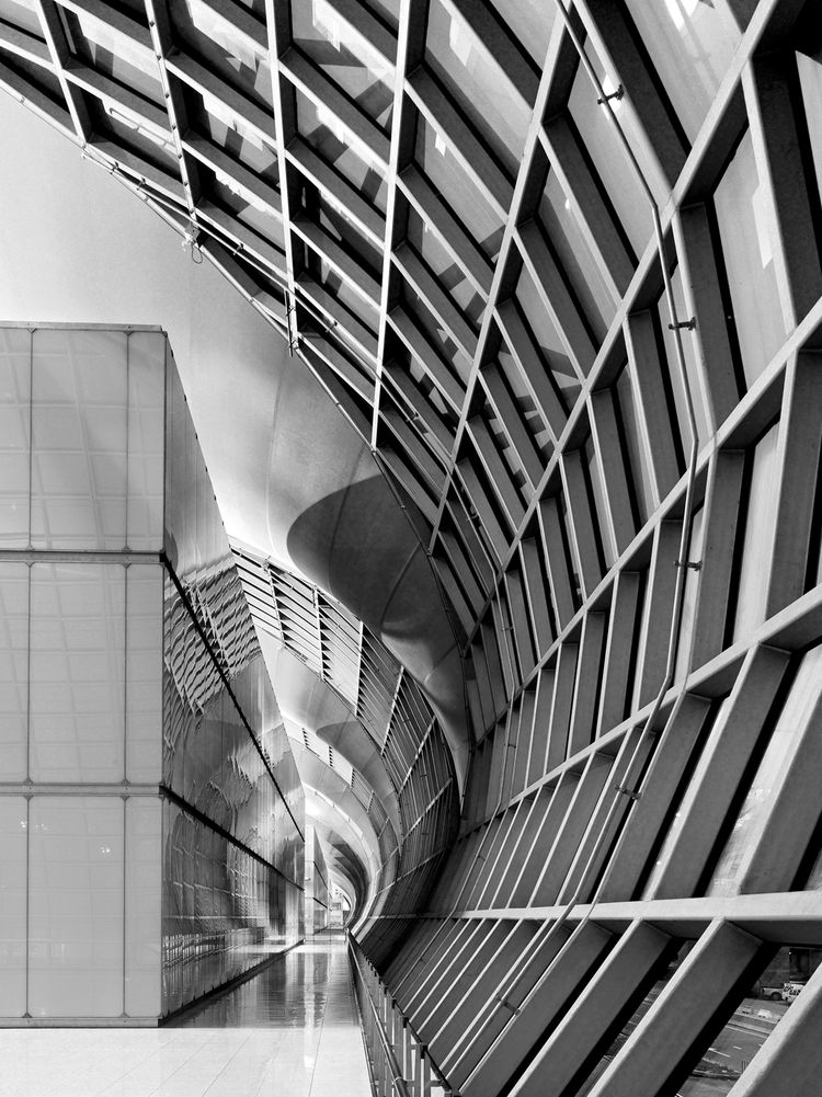 A concave surface inside one concourse of Suvarnabhumi International Airport is juxstaposed with a continuous vertical surface.