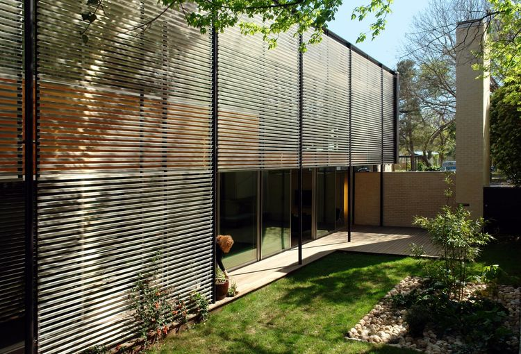 The west-facing exterior side wall is covered with an aluminum lattice rainscreen that controls sun pouring into the full-height windows beneath.