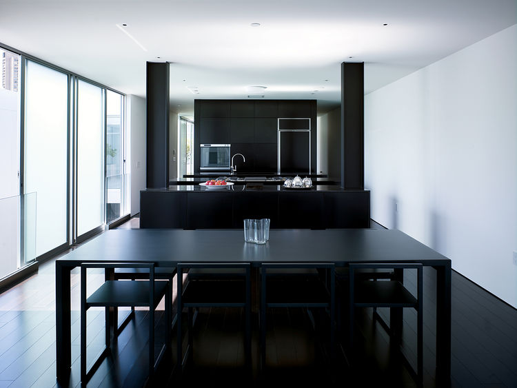 "The ""daytime"" living quarters in the penthouse are dark, from the floor to the furnishings. The dining table is by Jasper Morrison for Cappellini (with an Aalto vase by Iittala on top). The chairs are by Ag Fronzoni also for Cappellini."