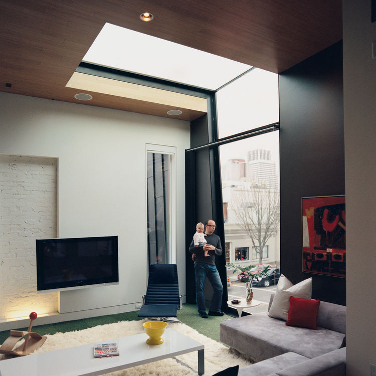 Architect Jeff Kovel and his daughter, Lola, bask in the swath of light afforded by 12 + Alder's signature window and skylight.