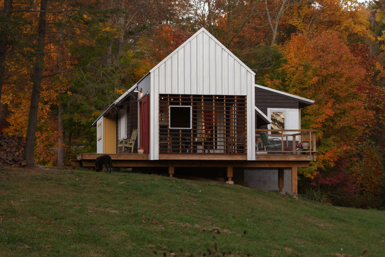 Red and yellow accent colors blend with natural North Carolina foliage. Cantilevered porches and decks provide deep shadows.