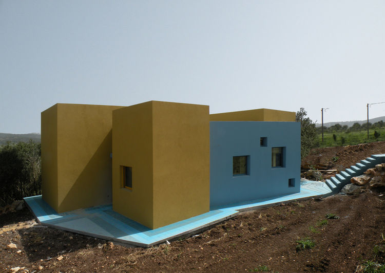 "The house sits on a slope, atop blue concrete and ceramic tiles. A set of web-shaped stairs (right) flow like a waterfall onto the blue floor.<br /><br />Photo courtesy <a href=""http://www.guyzucker.com/"">Z-A Studio</a>."
