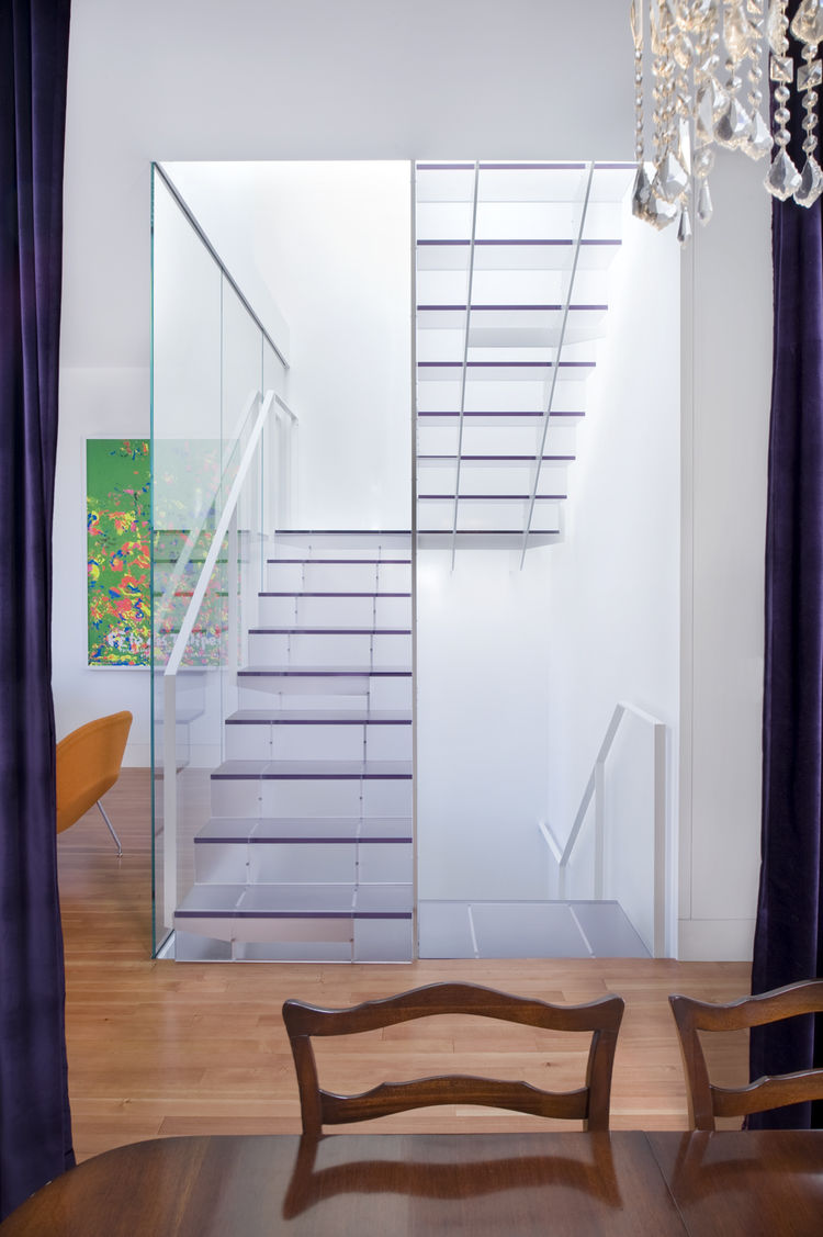 "The view of the stairs from the dining room on the main floor highlights the stairwell's function as a lightwell. Samaha and Hart chose one-inch-thick Ecorsein by <a href=""http://www.3-form.com/"">3Form</a> for the treads and risers, as it was the most tra"