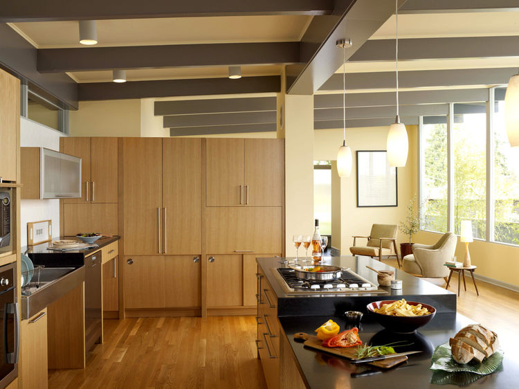 The kitchen cabinet wall provides storage and workspace, yet retains an open feel by stopping well beneath the ceiling. Sliding cabinets at the bottom reduce the number of space-hogging swinging cabinet doors, and a KitchenAid mixer is hidden behind the h